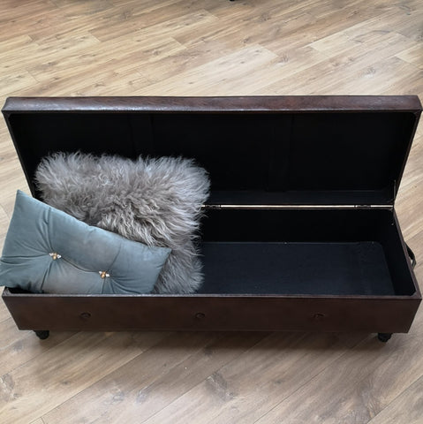 Large brown storage foot stool/ blanket box with a variety of cushions inside for display.