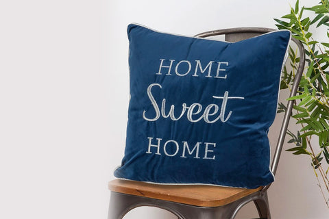 Royal blue home sweet home cushion resting on a wooden chair.