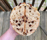 Load image into Gallery viewer, a round loaf of chocolate chip bread sliced in half