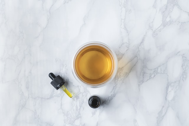 Cup of brown liquid with a tincture and dropper