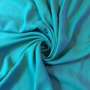 Vibrant Turquoise cotton blend, with a very nice drape and a soft touch. Easy to sew, beginners friendly.                                                                          Not stretch and not see-through.  Exact fabric content unknown.