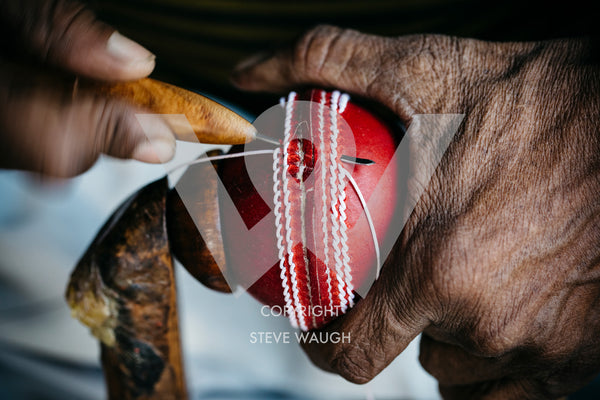 a close up image of a cricket ball being made at the Bat and Ball Factory, Meerut.