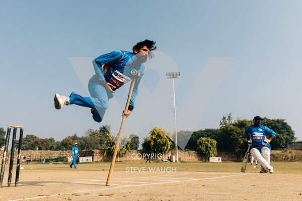 Photograph taken of a pole vaulting cricketer at the Physically Challenged Cricket Association of India.