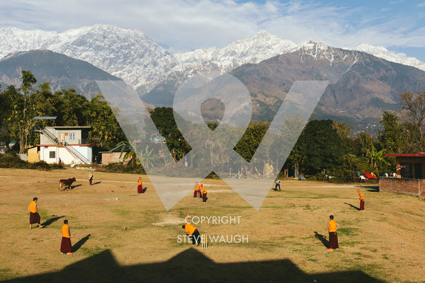 Photograph taken of a Monk cricket match in the foothills of the Himalayas.