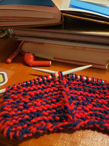 Knitting on needles with a headphone and a stack of books.
