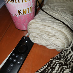 Knitters gonna knit cup with a knitting project, a fire stick  remote