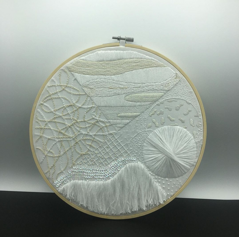 12 inch embroidery all in shades of white, bisected into quadrants, each quadrant is an abstraction of the four elements
