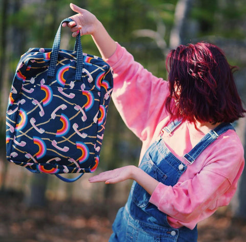 Gianna in overalls holds up her Maker totepack made from rainbows and telephone cotton canvas.