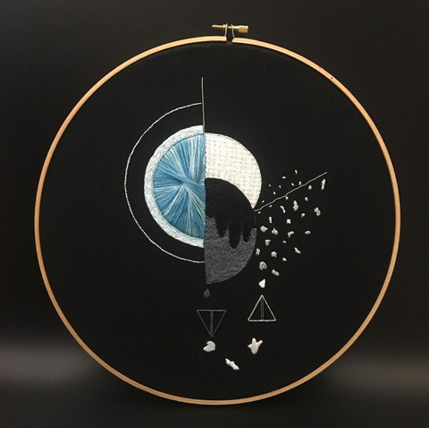 A twelve inch embroidery on black with a circle and beads dripping