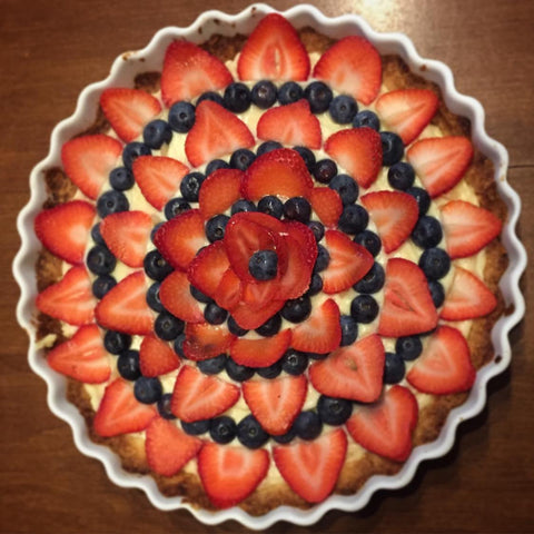 a fluted tart with circules of sliced strawberries and blueberries radiating out from the center