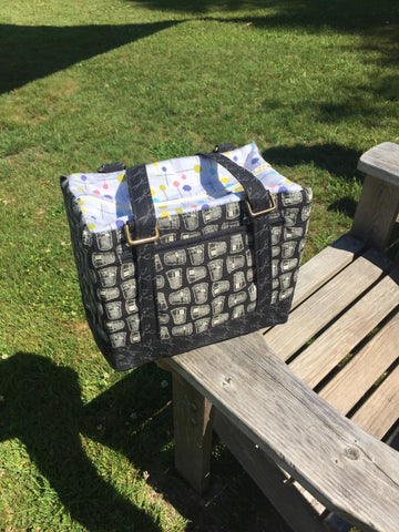 a fabric backpack lunch box in grey and lined in blue fabric sitting on an outdoor picnic table