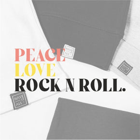 A close up of the PEACE LOVE ROCK N ROLL graphic design on a background of Have It All logo hem tags on t-shirts