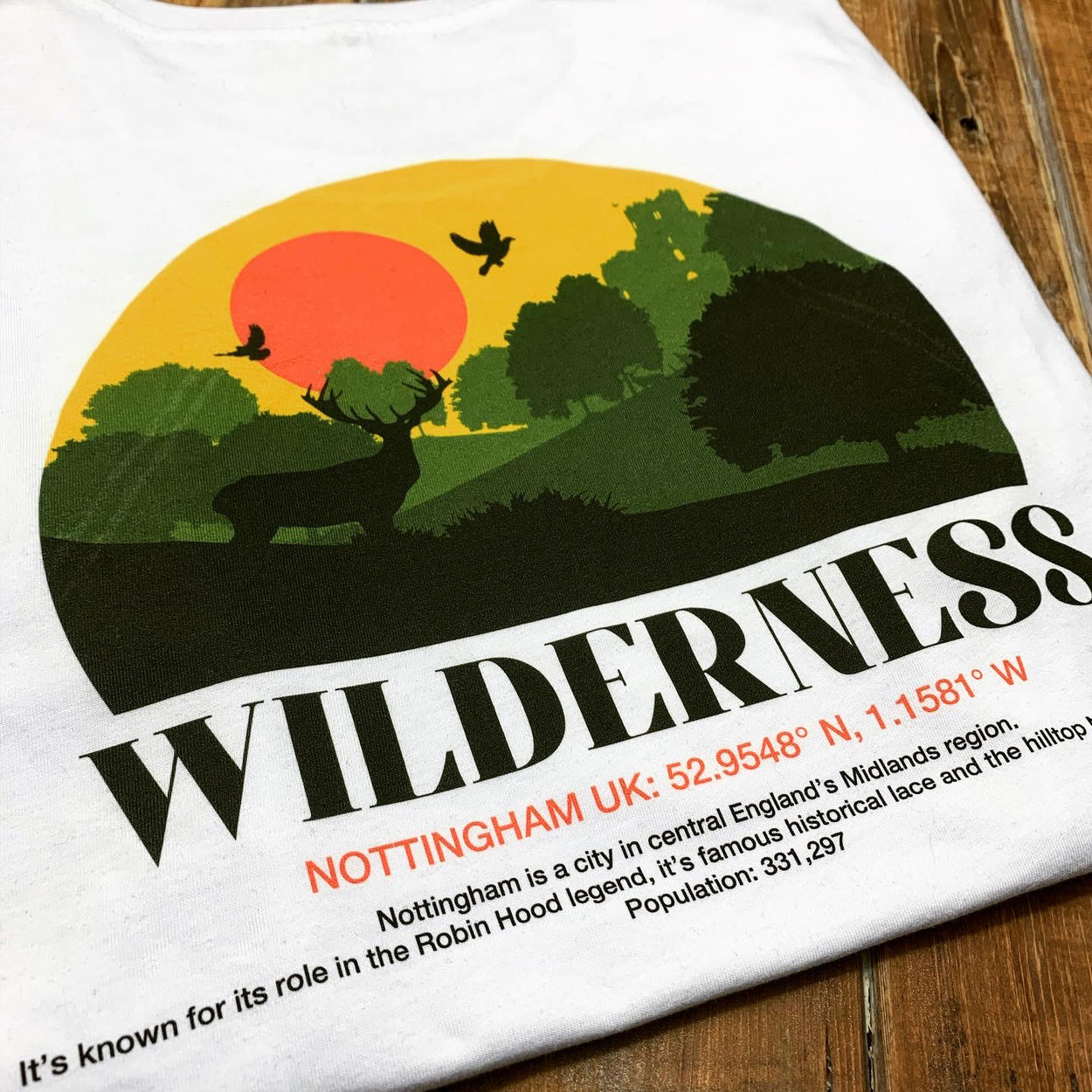 A close up image of a white short sleeve t-shirt folded and photographed on a wooden floor with a back print of a Wilderness design and a description of Nottingham's coordinates