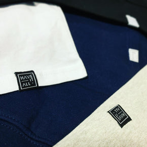 White, black, navy and heather grey coloured t-shirts piled on top of each other showing the Have It All logo on the sewn in hem tag at the bottom of each garment