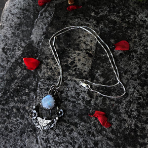 wide view of Moonstone and sterling silver handmade luna moth totem necklace with floral accents