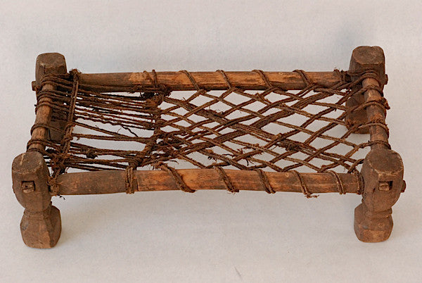 A circumcision bed of woven rope mesh over a wooden frame, with four flaring columnar legs