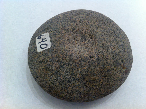 A large American Indian discoidal of speckled granite with a small dimple indentation on one side