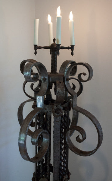 A pair of wrought iron lamps with four candles