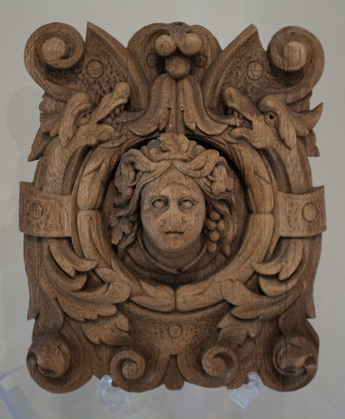 carved wooden plaques with Bacchus, God of Wine, surrounded by dragon figures.