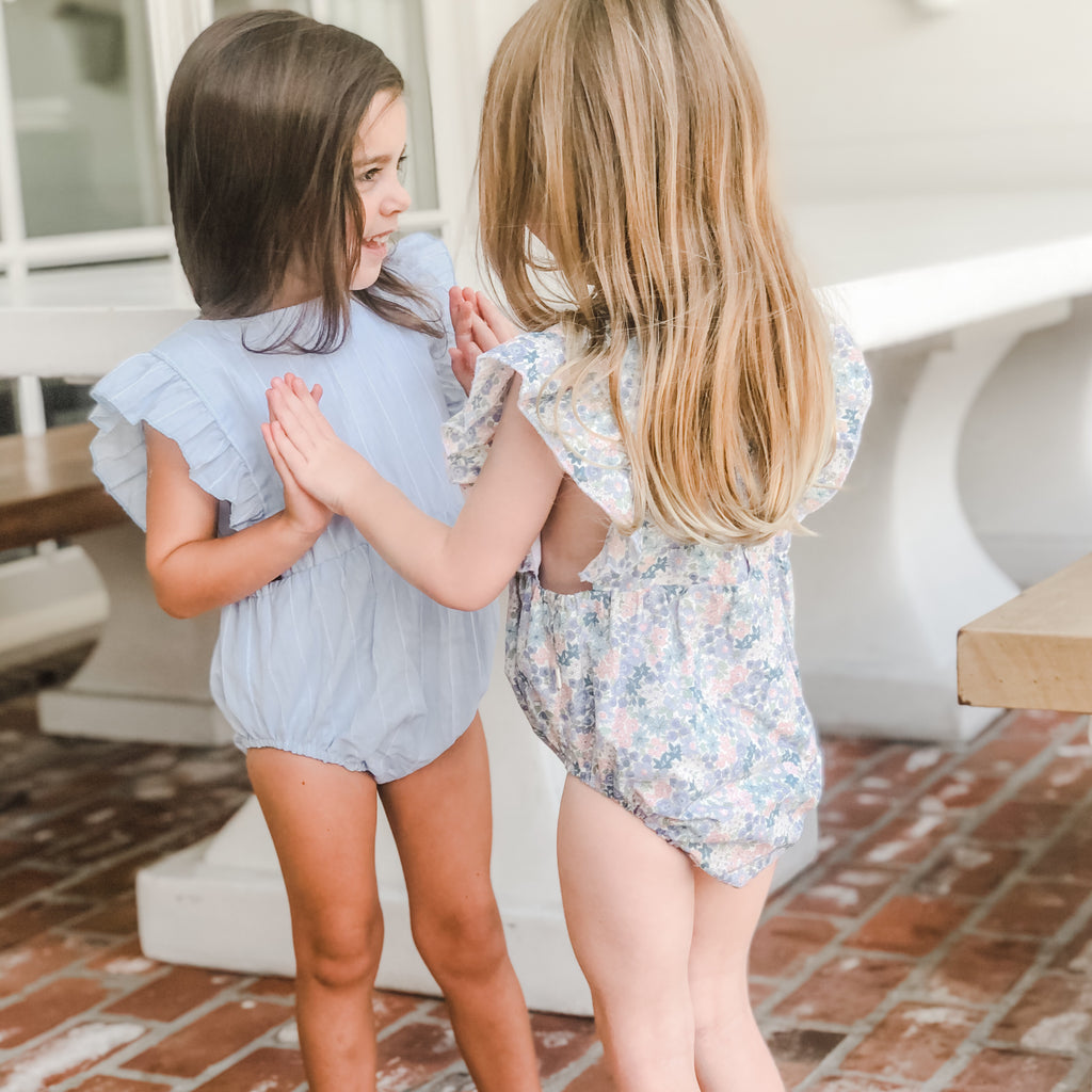 Girls playing Pat-a-Cake while wearing our Ruffle Sunsuits in the color Bloom and Pool.