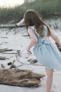 Girl exploring the beach in our signature double gauze cross back ruffle dress in the color Seafoam.