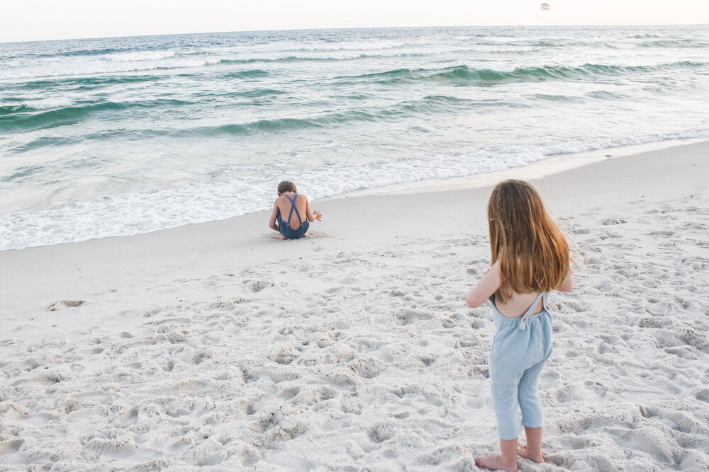 Playing in the sand while wearing our Super soft double gauze overalls in Seafoam and In Ocean.