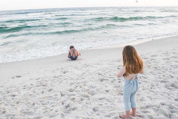 Watching the waves while wearing our super soft double gauze overalls in seafoam.