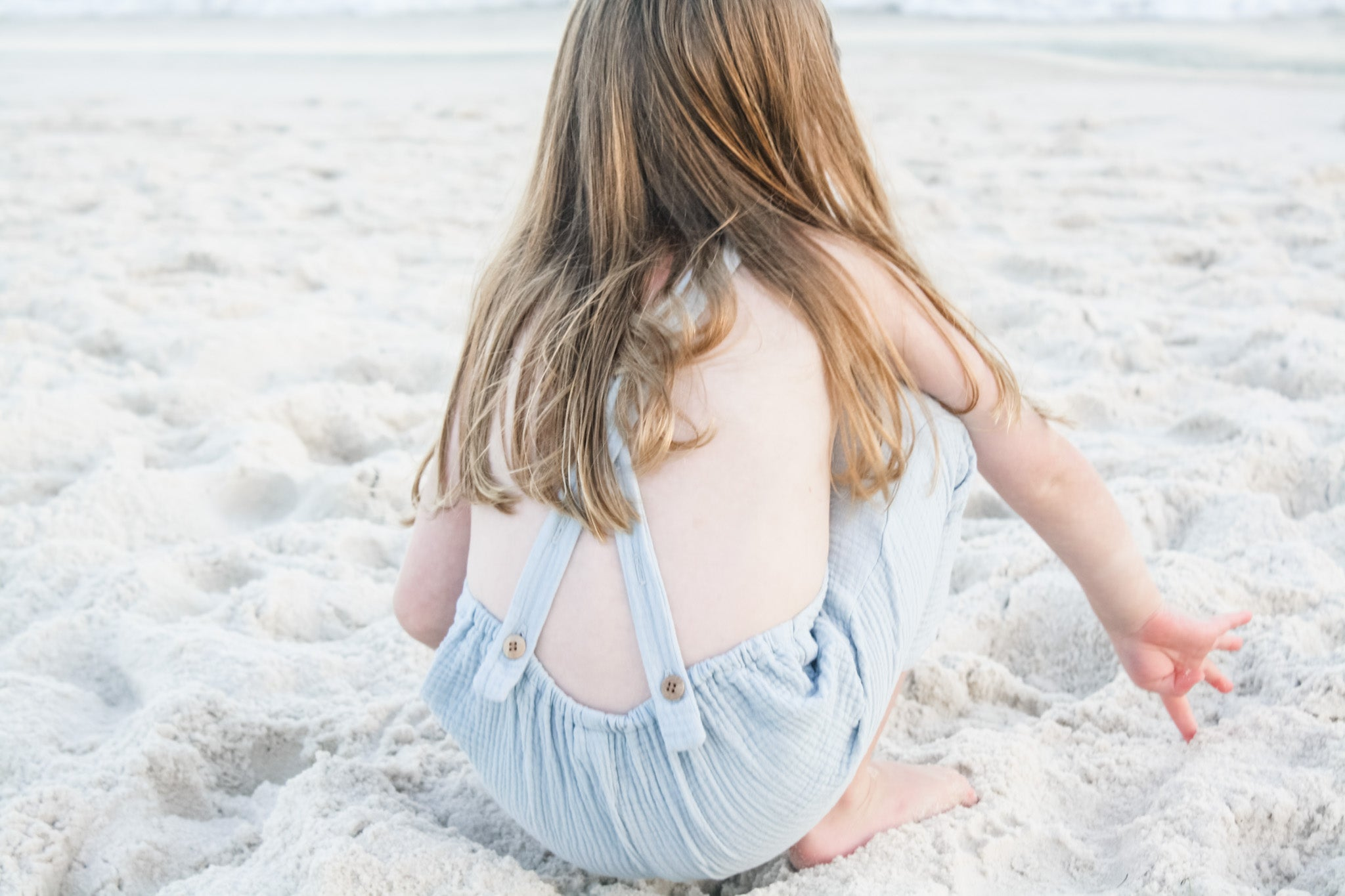 Playing in the sand while wearing our Super soft double gauze overalls in Seafoam.