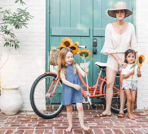 Our super soft, lightweight double gauze Pocket Tee in the color Shell paired with Racer shorts in Bloom. Another girl is wearing our Crossback Ruffle dress in Ocean while holding a sunflower. Their beautiful mother is wearing a swimsuit cover up and a hat.