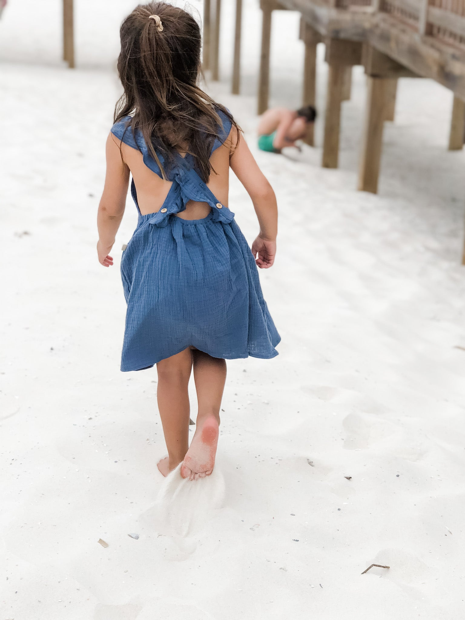 Girl wearing our signature double gauze cross back ruffle dress in the color Ocean while playing in the sand.