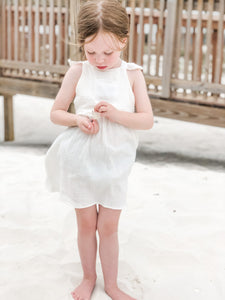 Girl playing with shells while wearing our signature double gauze cross back ruffle dress in the color shell.