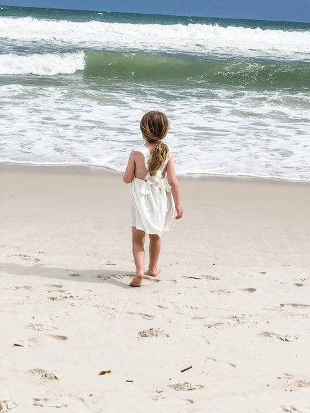 Girl watching the waves standing in the sand while wearing our signature double gauze cross back ruffle dress in the color shell.