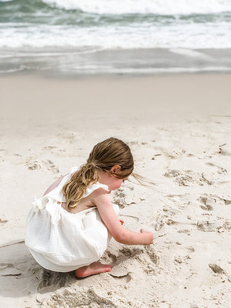 Girl playing in the sand while wearing our signature double gauze cross back ruffle dress in the color shell.