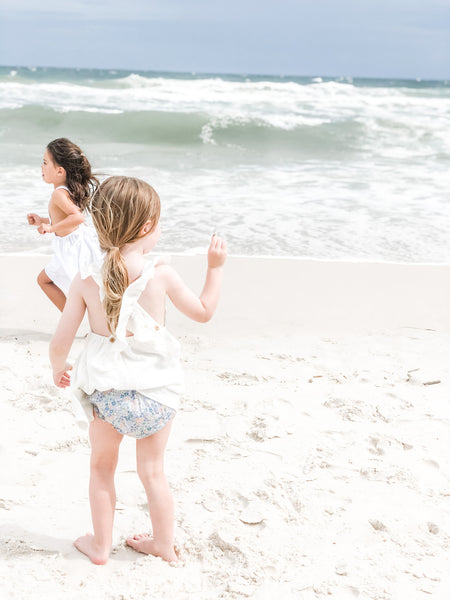 Our signature bloomers in the color bloom, paired with Ruffle dress in shell.  Children playing on the beach