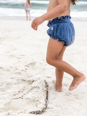 Our signature bloomers in the color Ocean playing in the sand.