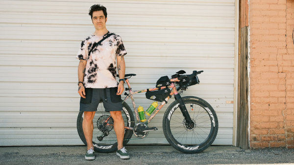 Nico posed in front of a garage door with his pink gravel bike loaded with gear