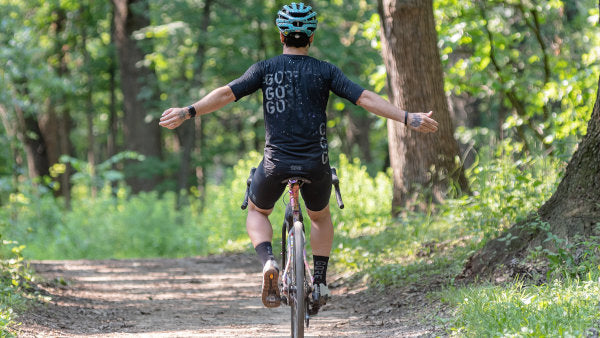 Nico riding away from the camera with arms out wide on a dirt trail line with trees