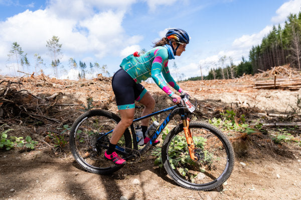Courtney riding her mountain bike on a dirt trail against roots and brush