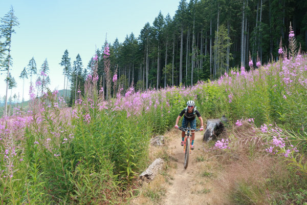Courtney riding a mountain bike on a dirt trail lined with tall wildflowers