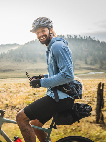 Jalen sitting on his gravel bike wearing riding gear and smiling in front of a mountain range