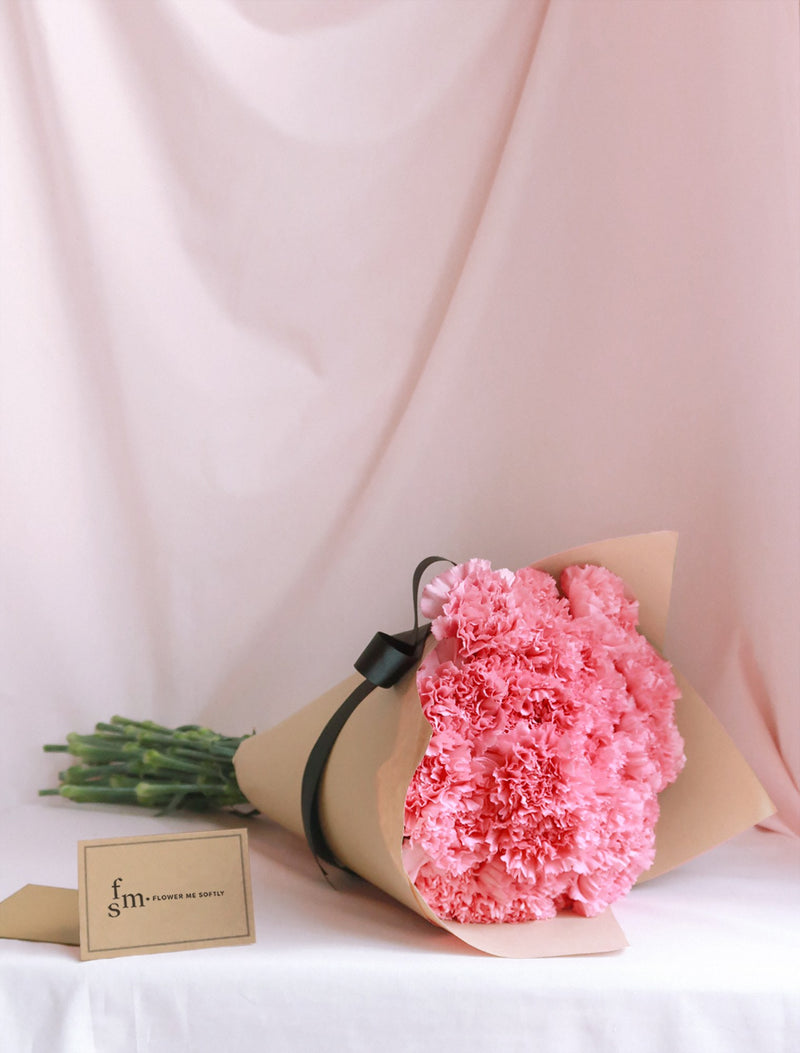 Carnation pink bouquet  in brown kraft paper with black ribbon. Delivered by Flower Me Softly