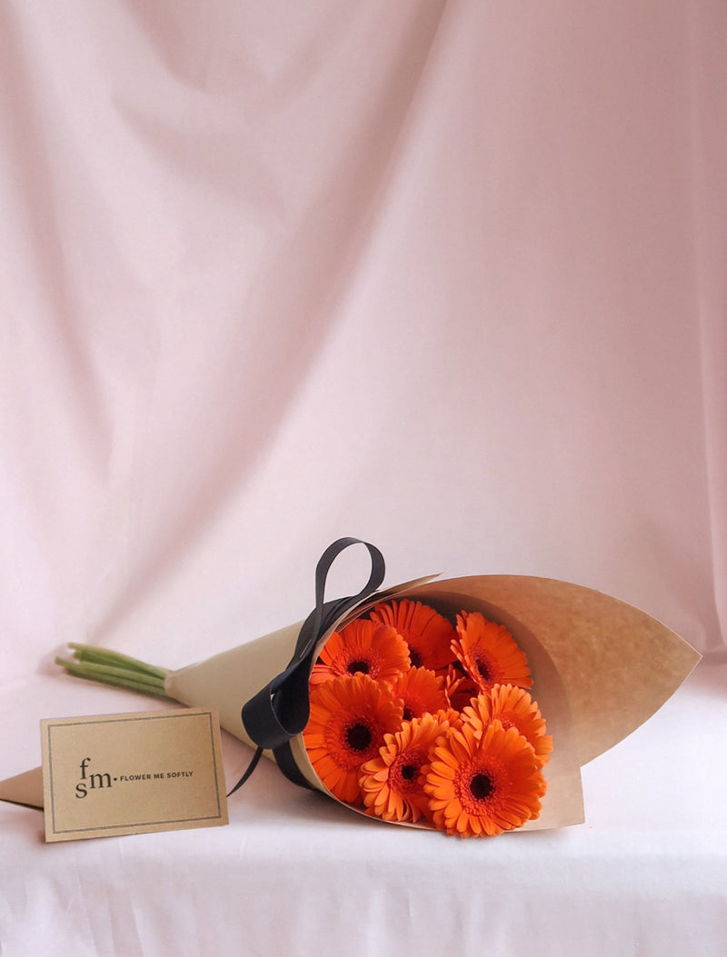 Gerbera daisies orange flower bouquet wrapped in kraft brown black ribbon. Flower Me Softly Melbourne Florist card.