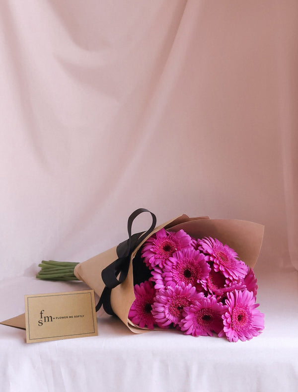 Gerbera daisies purple flower bouquet wrapped in kraft brown black ribbon. Flower Me Softly Melbourne Florist card.