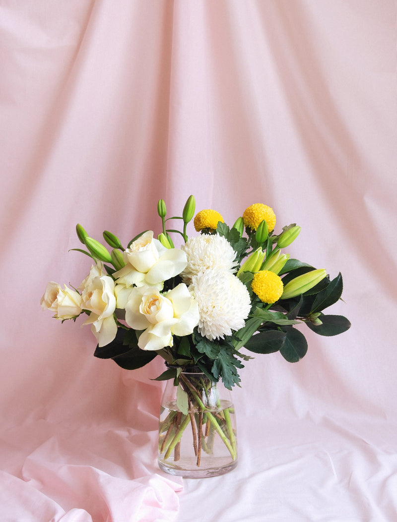 Lillies, white roses and yellow pin pong in a vase