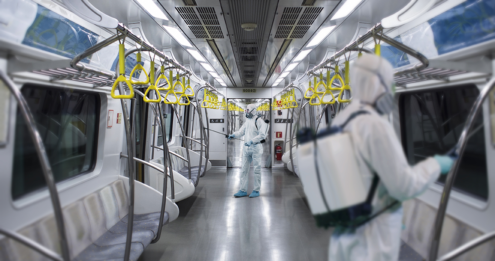 man in PPE clothing and sustainable mask disinfecting train carriage