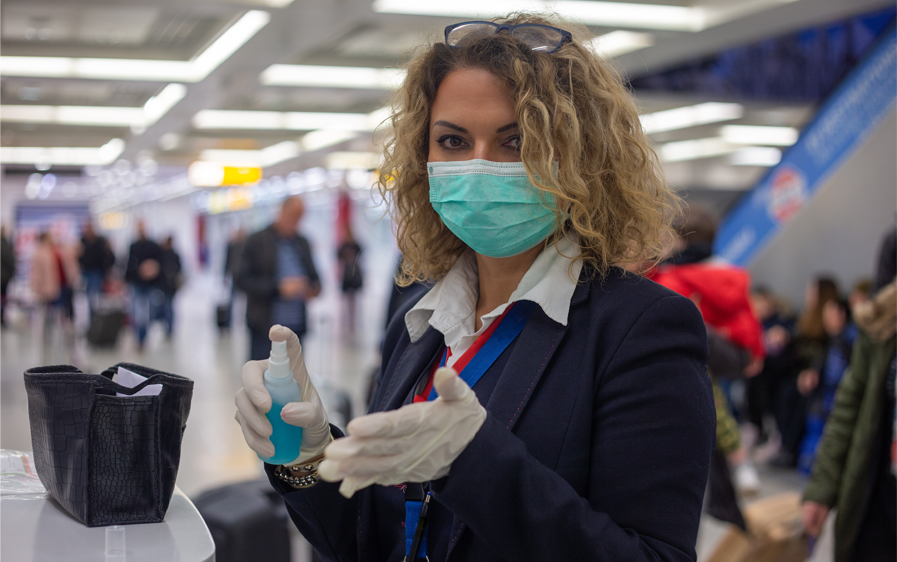 flight check-in attendant wearing PPE sustainable mask using hand sanitiser