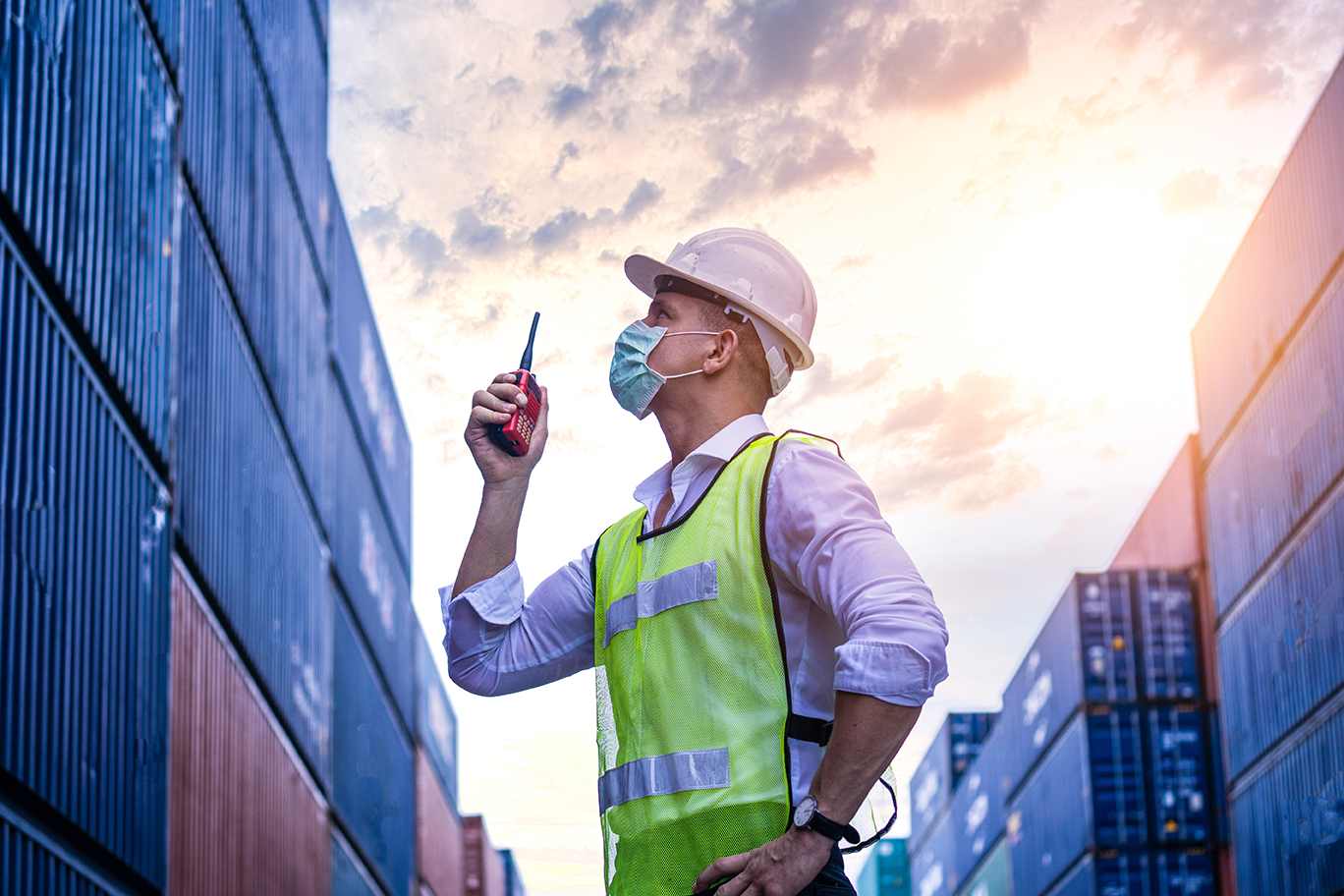 man in hard hat wearing PPE sustainable mask standing amongst shipping containers using a walkie talkie