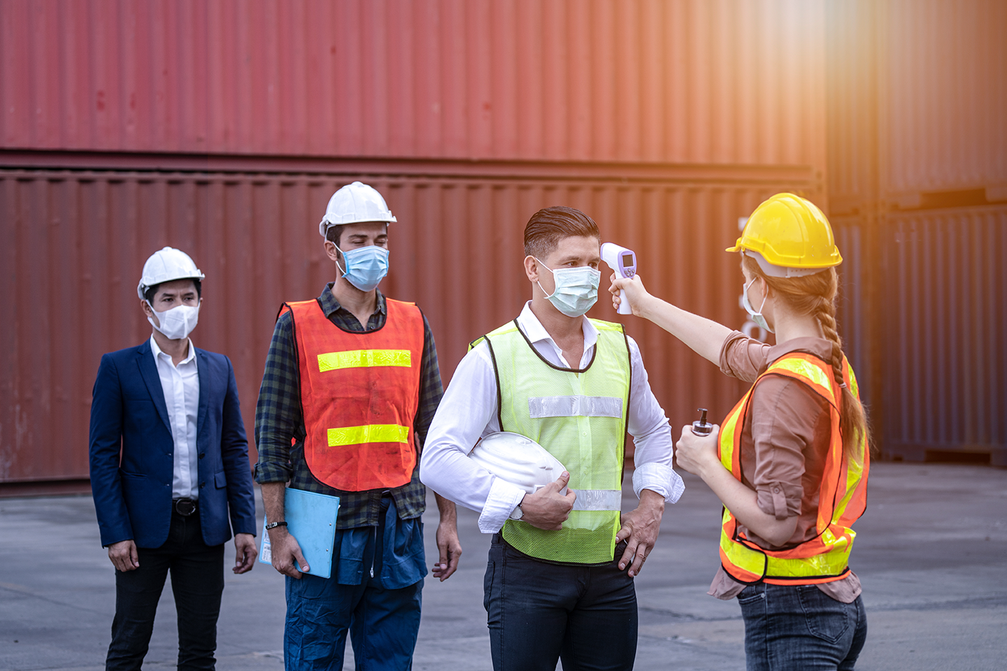 workers standing in line wearing PPE sustainable masks to be checked with a digital temperature device