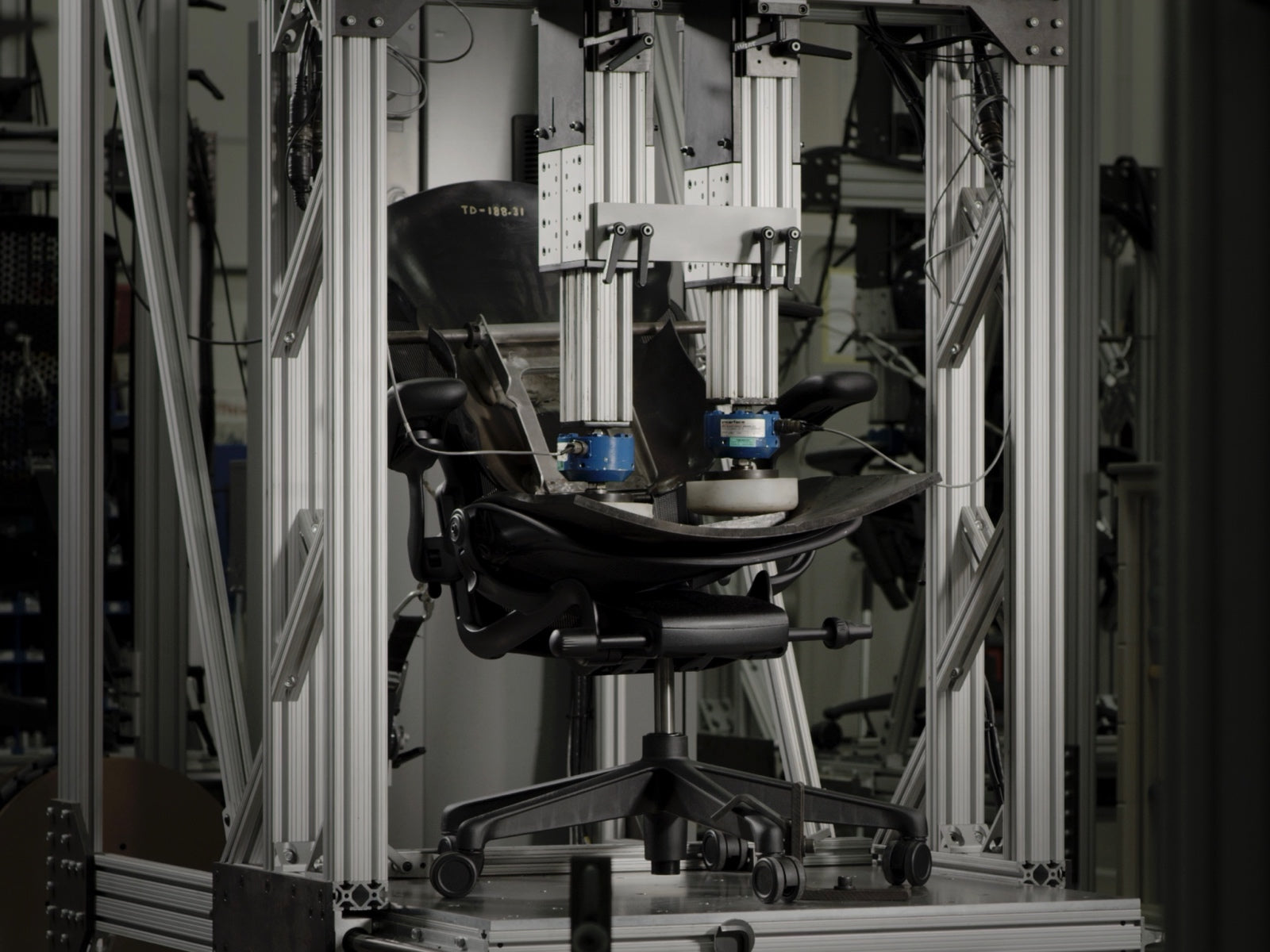 An Embody Gaming Chair, shown from the side, in a testing machine at the Herman Miller manufacturing site.
