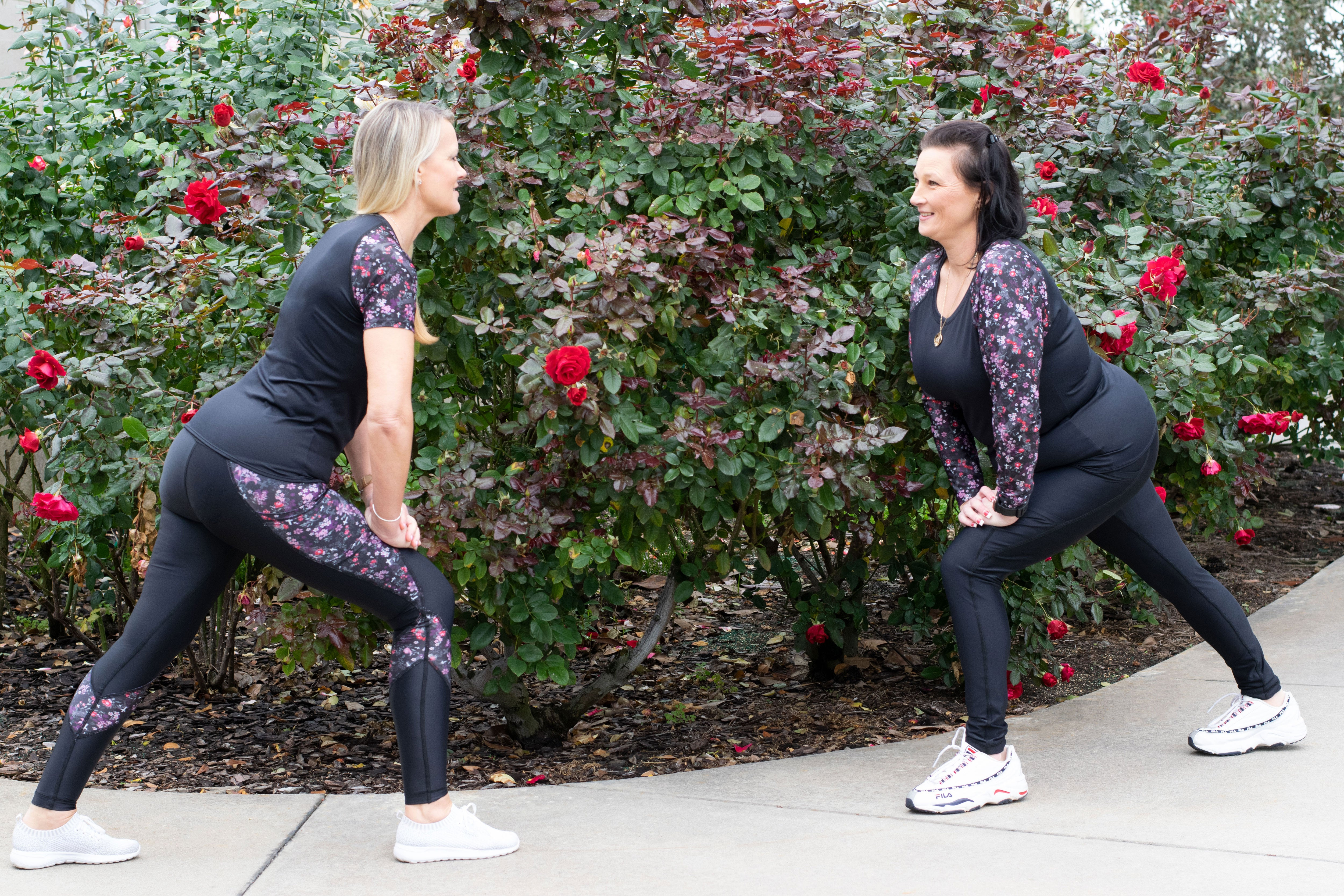 Two models stretching in front of a flower bush wearing Grace products